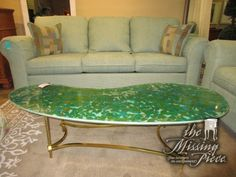 "Mosaic glass top coffee table in mix of blues and greens set on gold metal base. Whimsical piece to have in your living room! Love this shape as well; Very modern! 59""long x 24""wide x 15""high."
