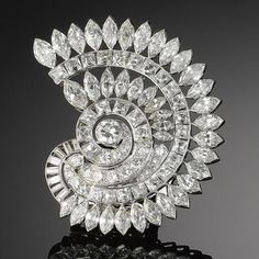 A diamond clip brooch, circa 1950 Designed as a nautilus shell, set throughout with old brilliant, brilliant, baguette, marquise and French-cut diamonds