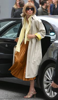 In Vogue: Anna Wintour looked elegant in a trench coat, golden brown pleated skirt and pastel yellow top