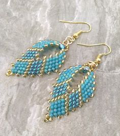"These earrings are already made and ready to ship. Shiny gold, frosted teal, and shiny teal Japanese glass seed beads are hand stitched together using the peyote technique creating a leaf shape. The frosted teal beads have a subtle iridescent rainbow finish. The beaded portion of the earring is approximately 1 1/2"" long. The total length of the earring is 2 1/2"" from the curve in the earring wire down to the very bottom tip. These earrings are very lightweight. Custom orders are always w..."