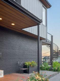 Double height entry, steel posts, spiral staircase, metal siding and a beautiful view