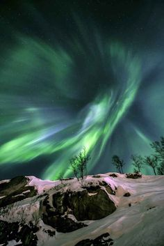 The aurora borealis twisted into a giant vortex above Grøtfjord in Norway. | 24 Awe-Inspiring Photos Of Earth And Space