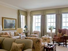 The large living room features a wide bank of windows with a spectacular view. Walls are painted in a neutral tone to complement the furnishings. Tailored silk window treatments frame the view.