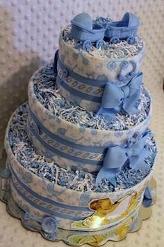 A Baby Diaper Cake in a twins boy theme was created using 70 Luvs sz. 1 diapers & 3 handmade flannel burp cloths. Attached to a 12 or 14 cake plate, the diapers were wrapped with the burp cloths and layered with blue grosgrain ribbon & satin ribbon with blue diaper pins. Tier tops decorated with blue and white mixed paper shred. Embellished with lots of blue party favors. The front embellished with a set of twin boys. Wrapped in protective cellophane decorated with blue & white cu...