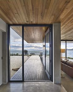 The dwelling's concrete slab meets a New Zealand pine deck at the custom steel entrance door.