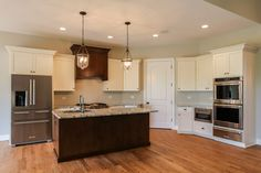 Custom two-tone kitchen with light outer cabinets and dark stained island with dark stained built-in kitchen hood vent.