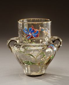 A translucent glass vase with heat applied handles, enamelled floral motifs and butterflies. Signed «E.Gallé Nancy». Circa 1900.