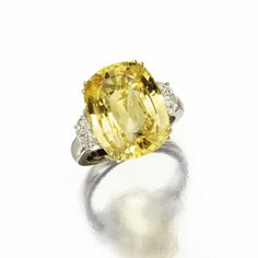 YELLOW SAPPHIRE AND DIAMOND RING The cushion-shaped yellow sapphire weighing 17.59 carats, flanked by 2 half-moon-shaped diamonds weighing approximately 1.10 carats, mounted in 18 karat white and yellow gold