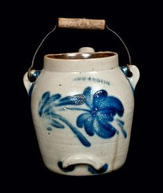 "Price Realized: $ 1,207.50  Cobalt-Decorated Stoneware Batter Pail, Stamped ""COWDEN & WILCOX / HARRISBURG, PA,"" circa 1865, ovoid pail with tubular pouring spout and metal-and-wood bail handle, decorated with a large spitting tulip on the reverse and heavy foliate brushwork around the spout. Provenance: A fresh-to-the-market example, consigned from Washington State. Some fry to cobalt on reverse. Two chips to spout. 1"" hairline in spout. Chip to rim. 1 3/4"