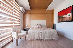In line with the modern style of the home, the master bedroom is also awash in neutral colors. The accent wall is covered with zebrano wood veneer cladding. The Noel Pascual painting with a bold red hue serves as a fitting final touch. Modern Bungalow House Design, Modern Room Design, Simple House Design, Modern House Philippines, Modern Family, Home And Family, Architectural House Plans, Dream House Interior, Minimal Home