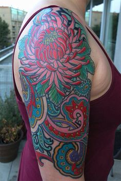 And a sea anemone in place of the flower and fish and make this a paisley sea shoulder tattoo with more blues, purples and turquoise.