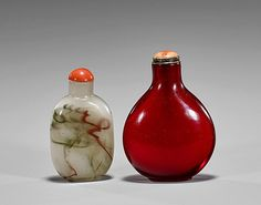 """<b>Two Glass Snuff Bottles</b> <br  /> Two glass snuff bottles: old monochrome ruby red circular form with polished coral stopper; together with rounded rectangular form with dark green, red, and brown """"ribbons"""" (chipping and wear); H: 3"""" (larger)"""