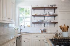 Interior Designer: Carla Aston  Like the darker (so not white) countertop for back counters, small bank of wooden shelves, the idea of pendants that are airy and don't interfere