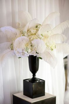 feather wedding centerpieces| The 1940s Add feathers to your flower arrangements for an Old-Hollywood glam feel. Black and white table settings complete the look.