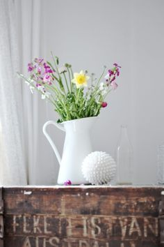 Flowers in the table in a pitcher.