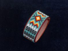 Native American Beaded Leather Bracelet With A Classic Cherokee Pattern In A Turquoise Background by LJ Greywolf
