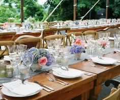 Mixtures of pink roses and peonies, blue hydrangeas and white sweet peas line the center of each table in silver vessels.