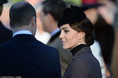 Kate wore her hair in a sophisticated braided low chignon and accessorised her pared-back look with a black hat and yellow drop earrings