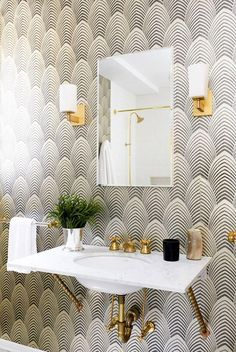 Black and white geometric print wallpaper in a bright white bathroom bathroom with gold sconces and brass sink fixtures -- love the contrast of black, white and gold, always!