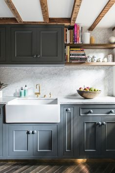 Kitchen: slate blue/grey Shaker cabinets, dark herringbone timber floor, farmhouse sink, gold/brass tapware, grey-and-white marble splashback and benchtop, exposed wooden ceiling beams, open shelving with books, gold kickboard/toekick, fruit bowl