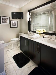Don't miss a beat with this classic black and white bathroom. A TV mounted in the corner allows for uninterrupted  TV viewing while getting ready in the mornings. A chic double vanity with marble countertops provides plenty of storage and space.