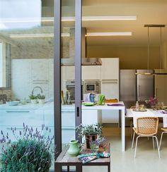 Cocina separada del jardín por cuarterones de cristal y hierro