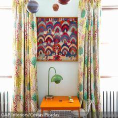 Farben und Muster wurden hier gekonnt gemixt. Ein geblümter Vorhang wurde mit einem rot-blau-gemusterten Wandteppich kombiniert. Der orangefarbene Tisch und  …