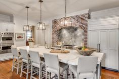 Fabulous kitchen features glass and iron lanterns illuminating super long island trimmed with red brick topped with thick marble countertops accented with dual basin sink lined with light gray barstools with nailhead trim.