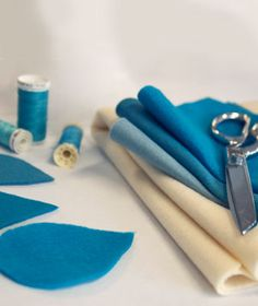 "What You Need •Raindrop and Cloud Templates •Scissors •1/4 yard of felt in various shades of blue •Fabric scissors •Blue thread •Sewing machine •1/4 yard white felt •Piece of cardboard approx 11"" x 16"" •Small amount of fiberfill (just enough to pad the cloud) •Straight pins •White thread •Large sewing needle •Hot glue gun and glue sticks •White heavy quilting thread or embroidery floss"