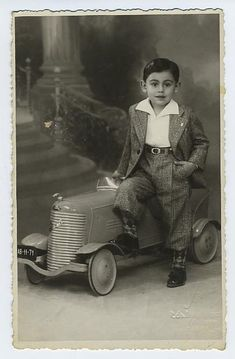 Vintage photograph of a very dapper young man with antique pedal car