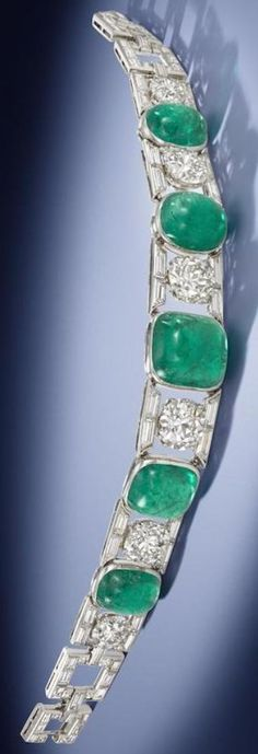 Chaumet - An Art Deco emerald and diamond bracelet, circa 1930. Set with five cabochon emeralds, of sugarloaf and oval shape, alternating with old brilliant-cut diamonds, between courses of tapered baguette-cut diamonds and baguette-cut diamond buckle-shaped links, emeralds approximately 25.00 carats total, Chaumet maker's mark, French assay mark. #Chaumet #ArtDeco #bracelet
