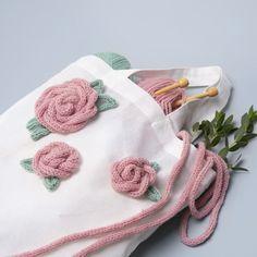 Koristele kangaskassi ruusuilla. Ruusut on tehty vauvalangasta nyörikoneella tehdystä nyöristä. Nyöri on ommeltu yhteen kukan muotoon. Poncho Crochet, Crochet Basket Pattern, Tote Bag, Free Pattern, Barbie, Diy, Fil Dmc, Tuto Tricot, Threading