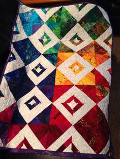 This is the scrap challenge quilt I made for my quilt store, Cozy Quilts. We had to use only our scraps; the white fabric was allowed extra. We also had to create our own design using the Strip Ruler Junior. I loved making it because in handling each fabric, I remembered each quilt I had made. I quilted it on my longarm with suns, moons and stars. These colors make me happy!