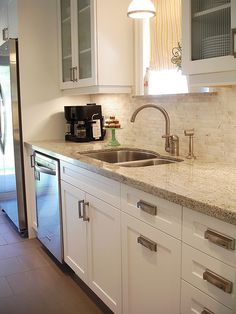 Wall colour: Baked Brie 780C-2, Behr  Countertop: Kashmir White Granite  Faucet: Rohl Single Lever C Spout Country Kitchen faucet, purchased on eBay  Backsplash: Venus Marble Mosaic in Milky Way from Olympia Tile  Floor Tile: Olive/grey porcelain tile (product # unknown) from Saltillo Tile