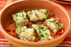 Baked cod on vegetable bed in a baking dish