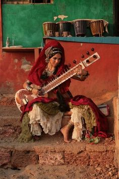 Sitar girl; I like the other angle better because I think that it captures the artist and she does not blend into the background as much