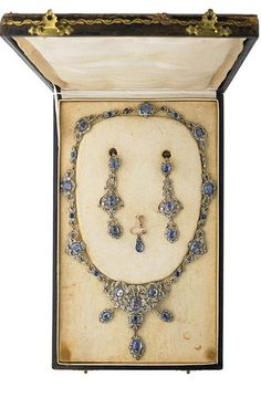 """VICTORIAN SAPPHIRE AND DIAMOND PARURE Fringe necklace and pendant earrings of silver topped gold, designed as ribbon bows with floral clusters, 30 round or oval mixed cut blue sapphires, approx. 28.0 cts. TW, and numerous rose cut diamonds, earrings with screw closures for unpierced ears, includes single similar earring. Necklace 18"""", earrings 3"""". Unmarked. 40.2 dwt. GW. In tooled Moroccan leather fitted box"""