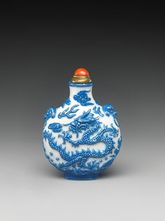 Snuff Bottle with Dragon Chasing a Flaming Pearl; eriod: Qing dynasty (1644–1911) Date: late 18th–early 19th century Culture: China Medium: Porcelain in imitation of glass with coral stopper Dimensions: H. 2 3/8 in. (6 cm) Classification: Snuff Bottles Credit Line: Bequest of Benjamin Altman, 1913