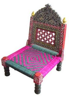 A traditional indian low seat chair with colourful weavings. The colours are bright, attractive and will bring life into any seating area.
