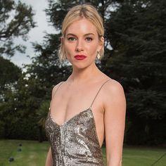 Look de Sienna Miller com vestido longo prata + batom vermelho.