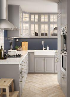 L alakú konyha hagyományos stílusú falakkal és alsószekrénnyel, szürke és üvegajtókkal.
