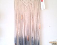 A handmade modern macrame wall hanging, wall art, dip dyed cotton in fresh bluish grey, on a wood dowel with painted white ends for a very clean look. Macrame wall hanging with a triangle shape pattern on a light coloured wood dowel. This piece is dip-dyed in an ombré soft blue. The sides of the wood dowel have been painted white to accent the soft blue of the fringe. Approximately 36 (92.4cm) long, from top of hanging to bottom of fringe. Wood dowel is 12 long. A soft and airy addition to…