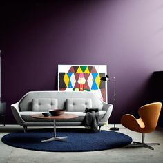 Modern interior with space age couch and dark, opaque purple walls.