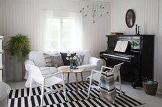 Oleskelutila on pelkkää raitaa. Vanha piano odottaa virittäjää,. Alvar Aallon tuolit ovat maakuntamatkailun tulosta, ne löytyivät edullisesti Turusta. Viisikymmentäluvun pikkupöytä on ostettu tuttavalta. Täysvillaisen Ikean maton puhtaana pito on helppoa.