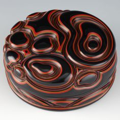 Kogo or container for incense in a compressed, circular form ornamented in deep relief with an abstract motif of rocks and swirling waves.Signed on the reverse with an incised signature by the artist: Yozei Kore wo Tsukuru or Made by Yozei (Tsuishu Yozei XX, the go or art name of Tsuishu Toyogoro, 1880 - 1952).