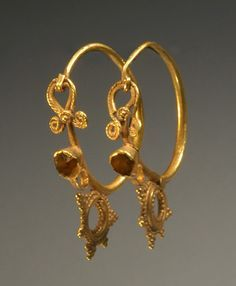 PAIR OF LATE ROMAN OR EARLY BYZANTINE GOLD EAR PENDANTS Inverted volutes over bezel; stationary beaded pendant on wire loop. 5th-6th Century AD