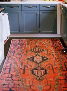 love those blue lower cabinets with red persian rug and dark hardwood floors.