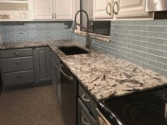 Beautiful Artic Ice Granite, Glass backsplash with black granite composite sink. Cabinets newly painted two toned, white and gray. Some new appliances. Bathroom Countertops, Granite Kitchen, Backsplash, Two Tone Kitchen, Kitchen And Bath, White Ice Granite, Granite Composite Sinks, Quartzite Countertops, Engineered Stone