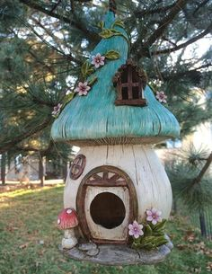 """A thatched storybook cottage will dangle from a tree bough to welcome feathered friends to nest inside. 11"""" resin"""