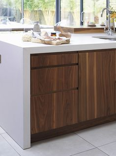 Handle-less walnut kitchen cabinets with wrap-over stone worktop